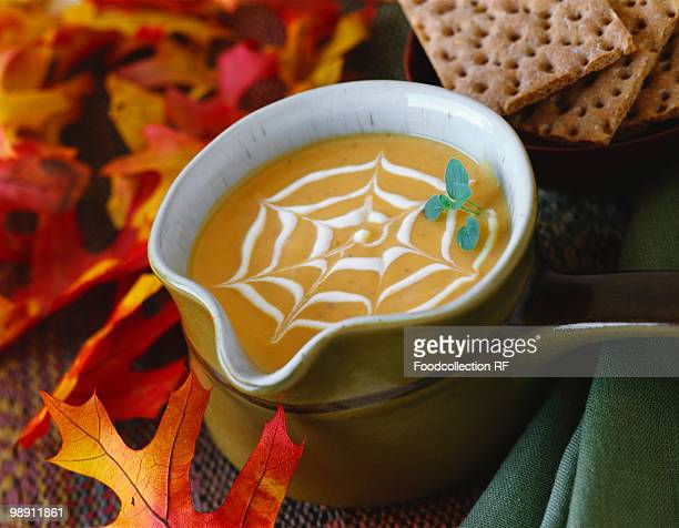 Cream of pumpkin soup with cobweb pattern & autumn leaves.