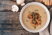 Cream soup puree with mushroom with toast bread on wooden background