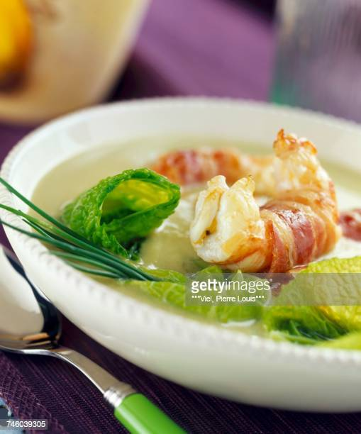 Creamed cabbage soup with langoustine prawns wrapped in bacon
