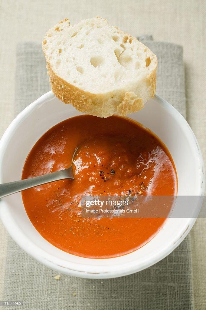 Creamed pepper soup in soup bowl, spoon & slice of baguette