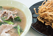 Creamy gravy Sauce with pork and crispy yellow noodle on the white table in Thai restaurant.