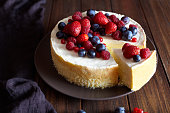 Creamy mascarpone cheese cake with strawberry and winter berries. New York Cheesecake. Christmas mousse dessert. Healthy food ration.