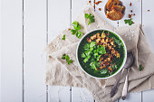 creamy spinach soup with fresh croutons and parsley, top view