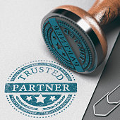 Trusted partner mark imprinted on a paper background with rubber stamp. Concept of trust in business and partnership.