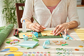 Flow of imagination: creative woman wrapped up in making colorful greeting cards for her friends while spending weekend at home, close-up shot