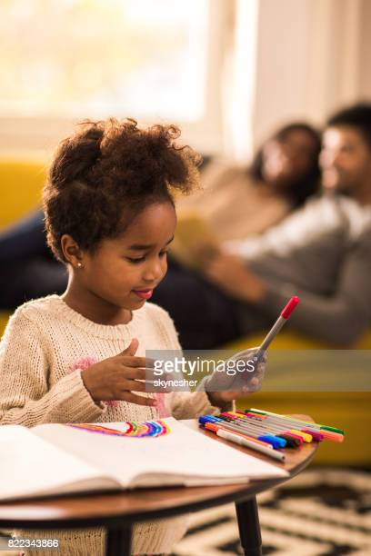 Creative African American little girl coloring on the paper at home.
