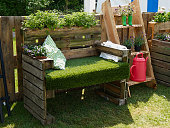 Creative bench made of old wooden pallets in a blooming garden