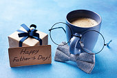 Creative breakfast on Happy Fathers Day with gift box, funny face from cup of coffee, eyeglasses and bowtie. Vintage style.