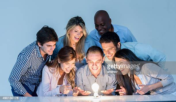 Creative business group looking at a lit light bulb