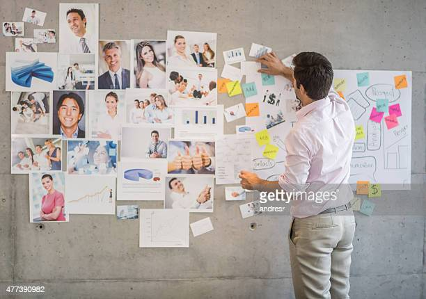 Creative business man creating a wall chart
