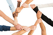 Directly above shot of people holding each other's hand in showing unity against white background