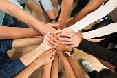 Directly above shot of creative business people piling hands over white background