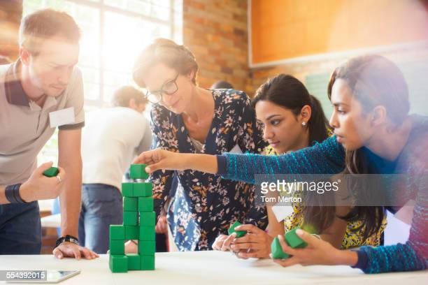 Creative business people stacking green blocks