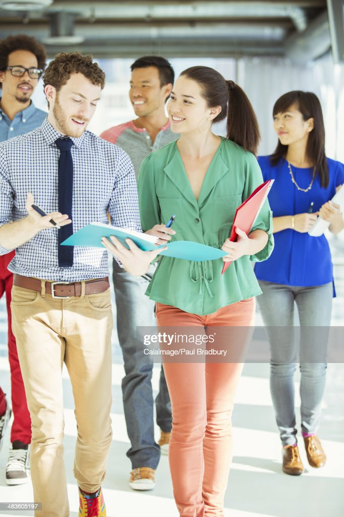 Creative business people with folders walking in office corridor