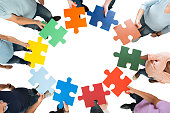 Directly above shot of team holding colorful jigsaw pieces in huddle against white background