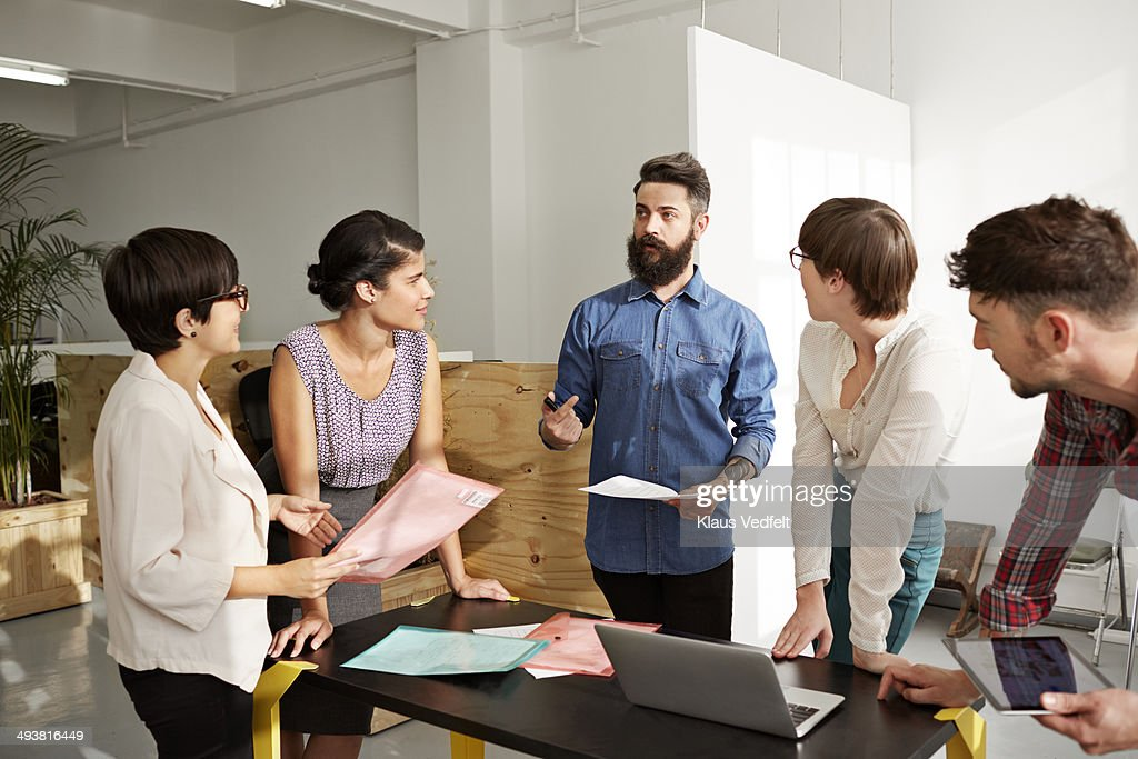 Creative businessman explaining to coworkers