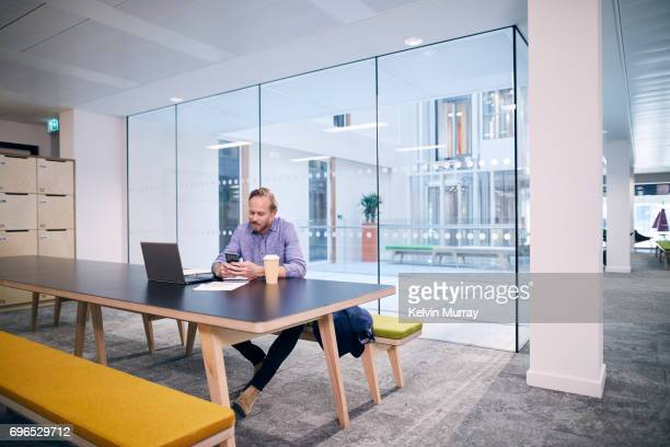 Creative businessman texting on cell phone in conference room