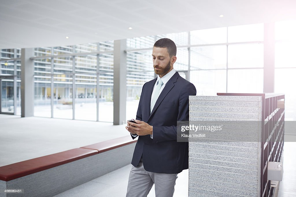 Creative businessman tjecking phone in hall : Stock Photo