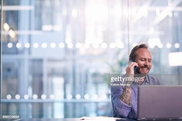 Creative businessman using cell phone in office