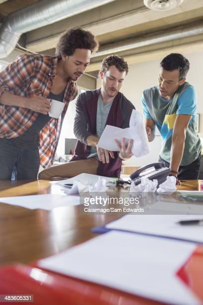 Creative businessmen reviewing paperwork in meeting at desk