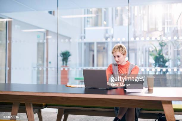 Creative businesswoman using laptop in conference room