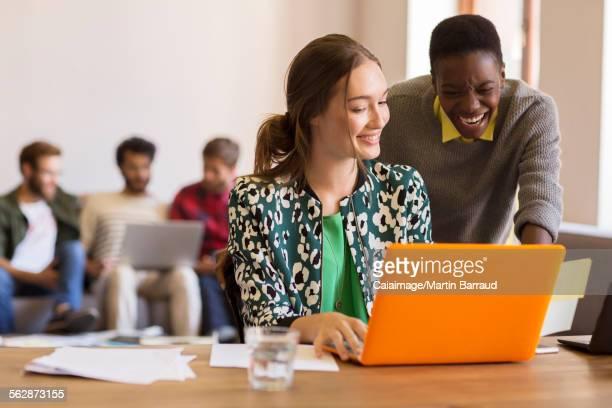 Creative businesswomen working at laptop in office