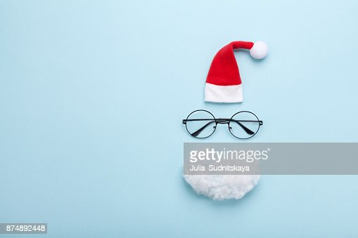 Creative christmas composition. Greeting card, invitation or flyer. Santa hat, beard and glasses on blue background top view. : Foto de stock
