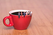 Creative concept about drinking coffee and waiting. Miniature people sit on the edge of a cup of coffee tea coffee break. Red cup on a wooden background.