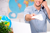 Close up photo of male travel agent. Young man talking on phone, smiling, proposing tourist booklet and looking at camera. Travel agency office interior with big world map. Focus on booklet