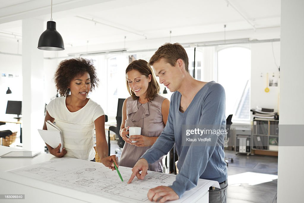 Creative coworkers discussing over blueprints : Stock Photo