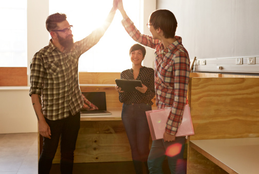 Creative coworkers doing high five at office