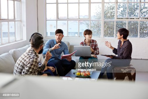 Creative coworkers having casual meeting : Stock Photo