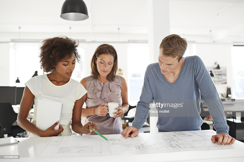 Creative coworkers looking at blueprints