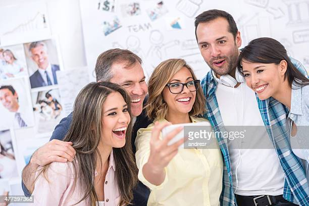 Creative coworkers taking a selfie at the office