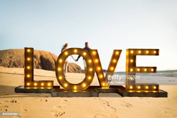 Creative creation of a love letters illuminated with light bulbs in front a happy couple in love walking in the Canary islands beach with nice light during travel vacations in Spain.