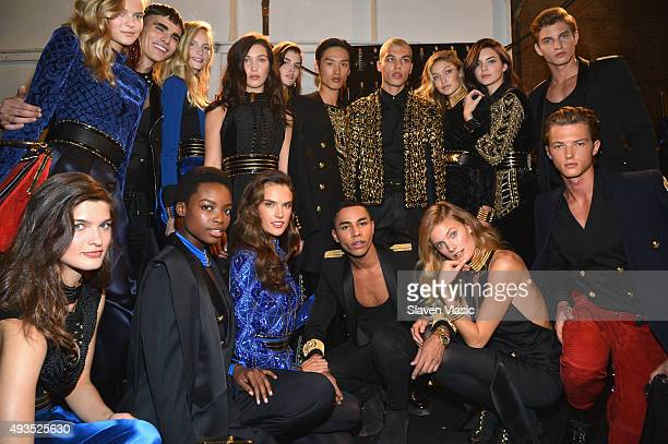 Creative Director for Balmain Olivier Rousteing poses with models backstage at the BALMAIN X HM Collection Launch at 23 Wall Street on October 20...