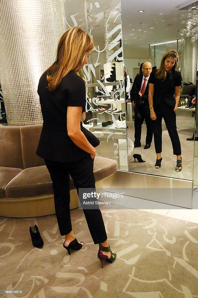 Creative Director of Marie Claire, <a gi-track='captionPersonalityLinkClicked' href=/galleries/search?phrase=Nina+Garcia&family=editorial&specificpeople=592222 ng-click='$event.stopPropagation()'>Nina Garcia</a> tries on a pair of Nicholas Kirkwood shoes during Marie Claire's Shoes First Shopping Event At Saks Fifth Avenue on October 3, 2013 in New York City.