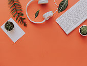 Creative flat lay of workspace desk, office stationery, keyboard, headphones and lifestyle objects on orange background with copy space
