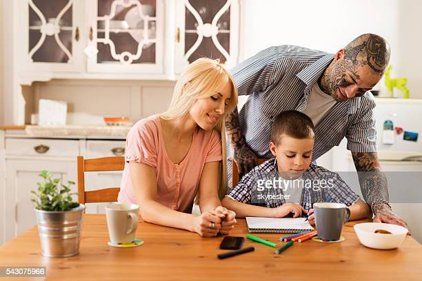 Creative little boy drawing at home with his parents.