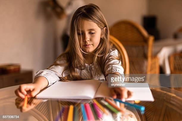 Creativa niña pequeña interior dibujo en la mesa de comedor.