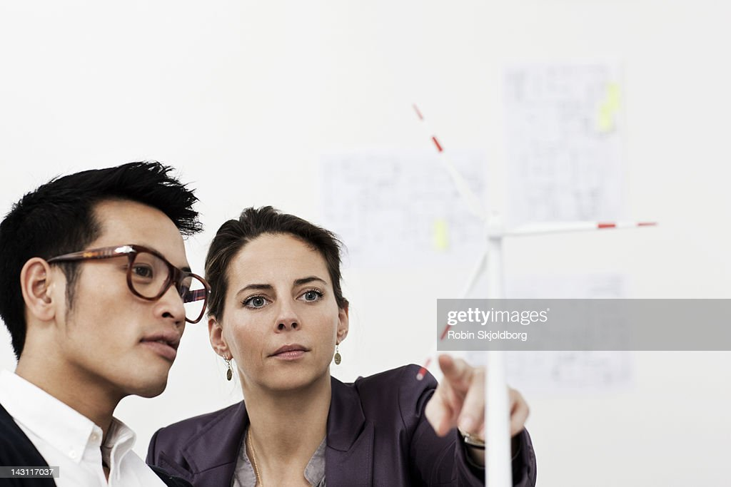 Creative man and woman looking at wind turbine : Stock Photo