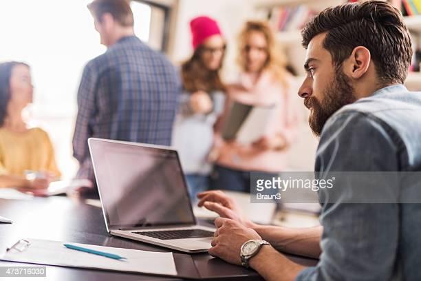 Hombre creativo, trabajando en la computadora portátil con sus colegas en fondo