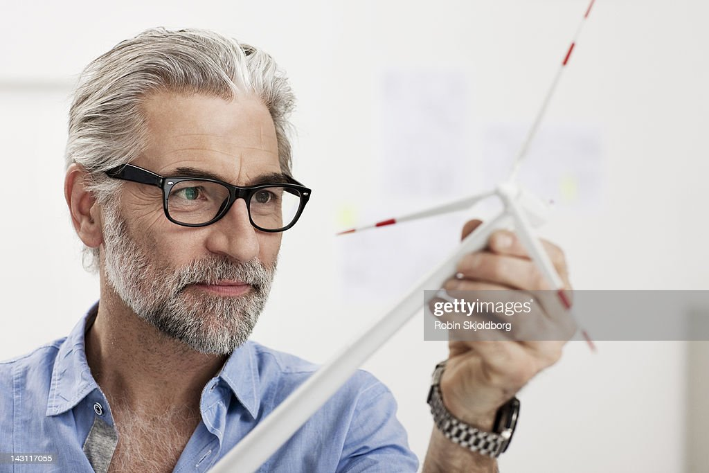 Creative mature man looking at wind turbine : Stock Photo