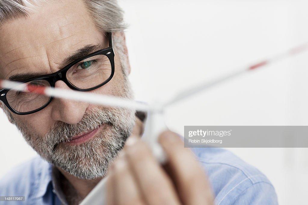 Creative mature man looking at wind turbine