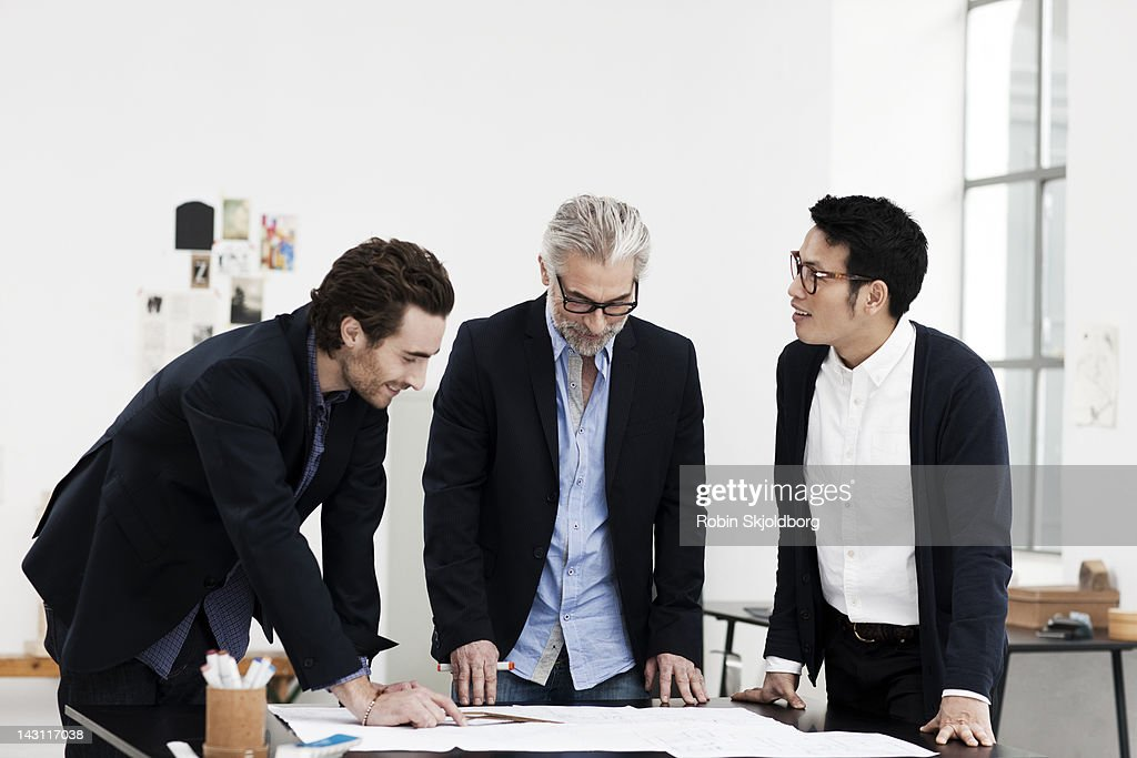 Creative men looking at sketches : Stock Photo