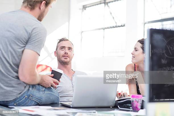 Creative office people having a casual team discussion and sitting on a desk