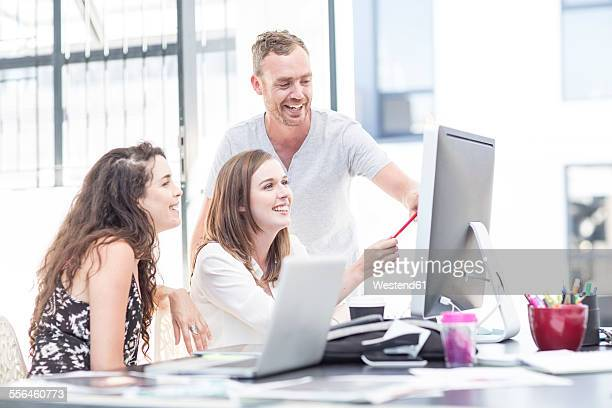 Creative office people having a discussion on a computer