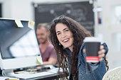 Creative office woman offering takeaway coffee