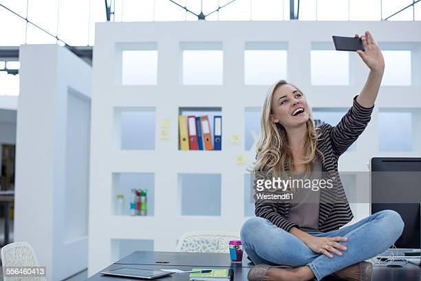 Creative office woman sitting on her desk taking a selfie