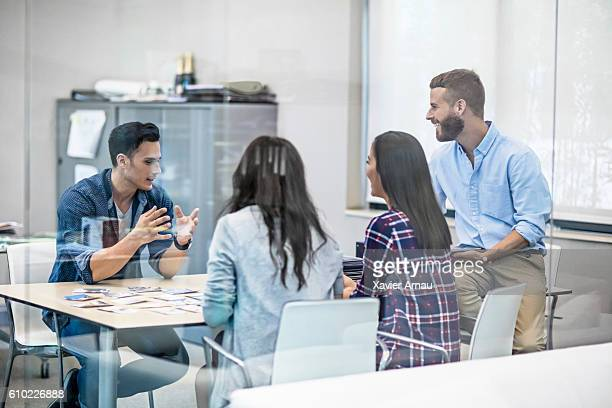 Creative people reviewing picture designs in office meeting
